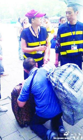 高清图—武昌区武珞路民工扔烟头捡起后下跪求城管